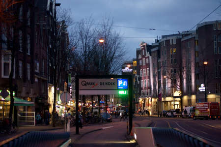 nightshot: Amsterdam Netherlands December 31 2014: The city of Amsterdam in the evening with a lighted parking sign and shops on December 31 2014 in Amsterdam. Editorial