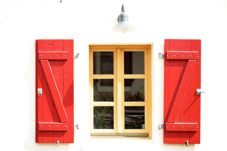 colored window: Bright red colored shutters on a nostalgic window.