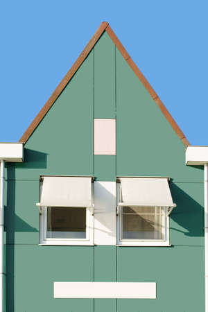 gable: A Dutch house with a triangular gable, roof gutters and sunscreen.
