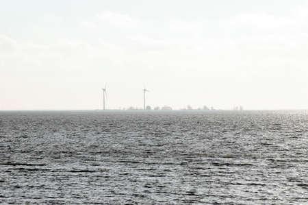 ijsselmeer: The sea, the Ijsselmeer in the Netherlands with an island and wind turbines on it.