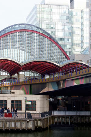 hamlets: London, UK - November 29, 2014: Pedestrians walk along a promenade under the modern bridge construction of the underground station Canary Wharf in the London Borough of Tower Hamlets on November 29, 2014 in London. Editorial