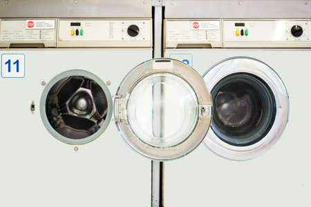 operating key: Two juxtaposed washing machines in a laundromat.