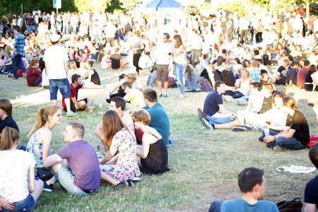 listeners: Mainz, Germany - July 09, 2015: Young viewers and listeners sitting on a meadow at a concert at the Asta Summer Festival on July 09, 2015 in Mainz.