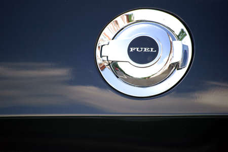 car body: A chrome and shiny tank cap edged in a car body.