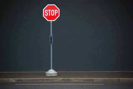 homogeneous: A stop sign stands in front of a homogeneous wall on a sidewalk.