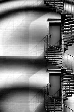 A spiral staircase, fire escape on the side of a industrial building facade.