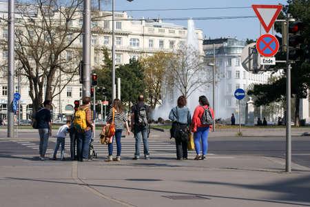 semaforo peatonal: Viena, Austria - 30 de marzo 2014: Los peatones se enfrentan a los semáforos en el centro de Viena, frente a la fuente de la Vienna Schwarzenbergplatz el 30 de marzo de 2014 en Viena.