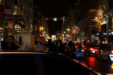 festively: Paris, France - December 30, 2013: A police operation in a festively decorated street in downtown Paris with a jam on December 30, 2014 in Paris.