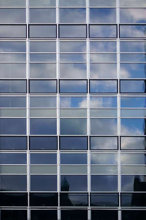 modern buildings: The facade of a modern office building with clouds reflections in the windows. Stock Photo