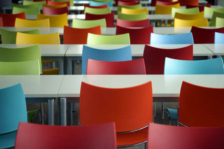SILLA: Filas vac�as de asientos con mesas y sillas de colores en el espacio de una instituci�n educativa o en la escuela.
