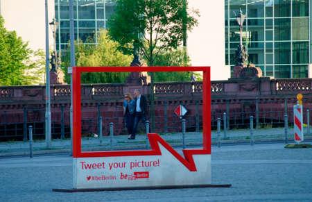 tweet: Berlin, Germany - June 04, 2015: Pedestrians crossing a picture frame of the Tweet Your Picture action Berlin on June 04, 2015 in Berlin.