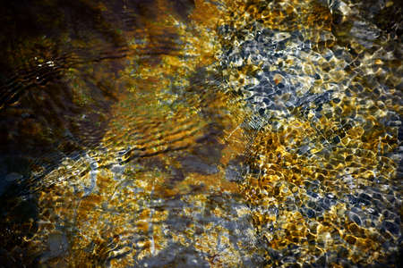 fluctuations: A stream of smooth slate stones and with gold-colored deposits generated different wave structures on the water surface.