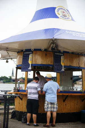 buying stock: Mainz, Germany - July 11, 2015: Two people standing at the beer stall of the Flensburg Brewery and buying a beer on July 11, 2015 on the Festival Beer stock in Mainz.