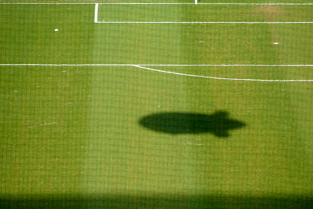 safety net: The green lawn of a soccer field with markings behind a safety net and an abstract airship shadow.