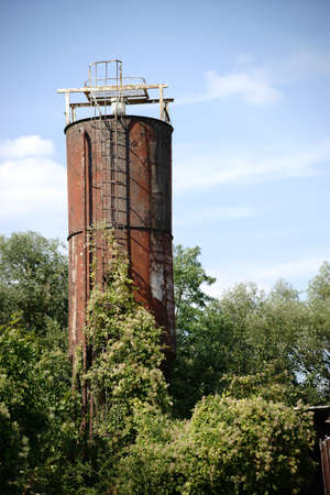 storage tank: An old rusted storage tank or silo is overgrown by bushes.