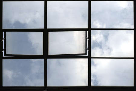 sunroom: Through a glass roof, consisting of tilt windows and windows, shines the blue cloudy sky. Stock Photo