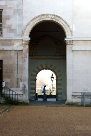 passerby: London, UK November 29, 2014: A passer-by crosses on arched gateway at the Royal Naval College in Greenwich on November 29, 2014 in London.