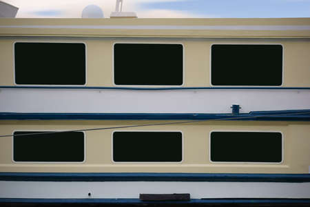 starboard: The side view of a passenger ship, starboard, with windows and railing. Stock Photo