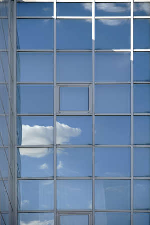 struts: A white cloud and reflections in the window of a modern facade.