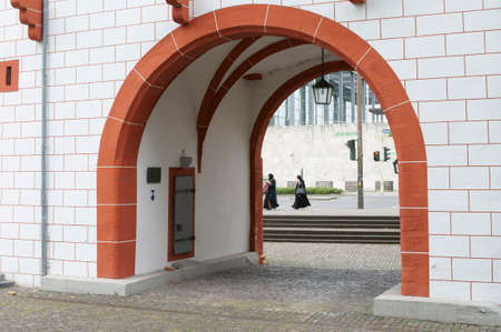burqa: Two women in burka crossing a street behind an archway of the iron tower in Mainz. Stock Photo