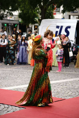 intercultural: Mainz, Germany - September 25, 2015: A Kurdish woman holding a child in her arms and presented a colorful costume at an event organized by the Intercultural Weeks on September 25, 2015 in Mainz. Editorial