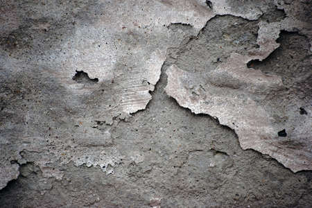 flaking: A flaking plaster layer on the surface of a concrete wall can be used as background. Stock Photo