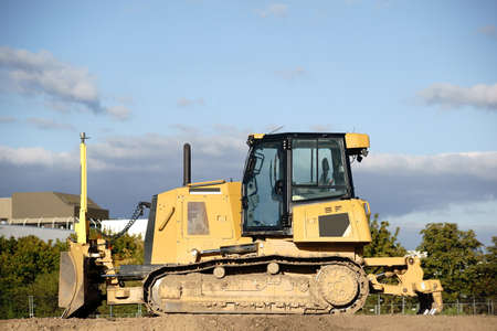 A bulldozer or a crawler placed on a mound of earth.