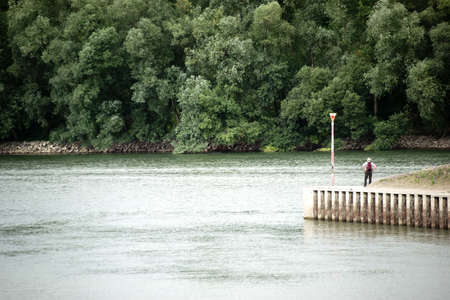 riparian: A hiker looks on the waters of the river Rhine and seems to be small in contrast to the surrounding.