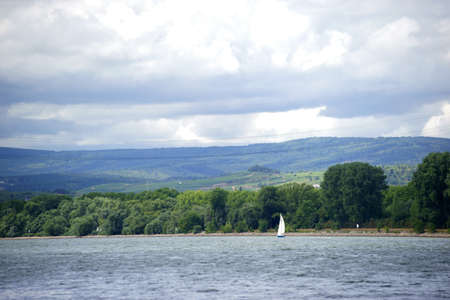 river scape: A sailboat sailing on the river Rhine in front of of the Taunus mountain range during a weather change.