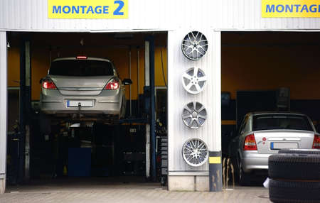 An auto repair shop with two garages and two cars on lifts.