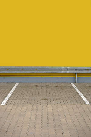 guardrail: A single parking lot with markings and a guardrail at the end.