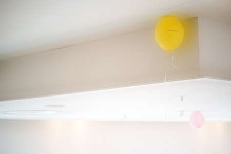 safety slogan: Two balloons on a ceiling with plates and panels and a sprinkler system.
