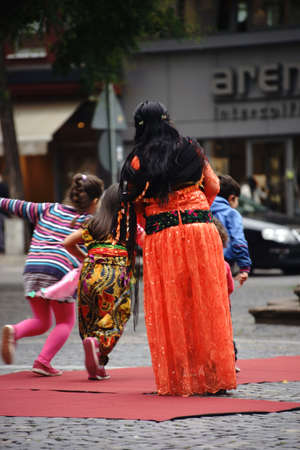 intercultural: Mainz, Germany - September 25, 2015: Three Kurdish children playing in front of a Kurdish woman in a traditional costume at an event of the Intercultural Weeks on 25 September 25, 2015 in Mainz. Editorial