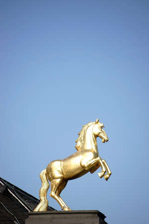 mainz: Mainz, Germany - October 02, 2015: The golden Ross sculpture on the roof of the main museum Mainz in the sunlight on October 02, 2015 in Mainz. Editorial