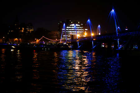 London, UK - NOVEMBER 29, 2014: The illuminated nocturnal Hungerford Bridge over the River Thames with the Charing Cross railway station on 29 November 2014 in London. Editorial