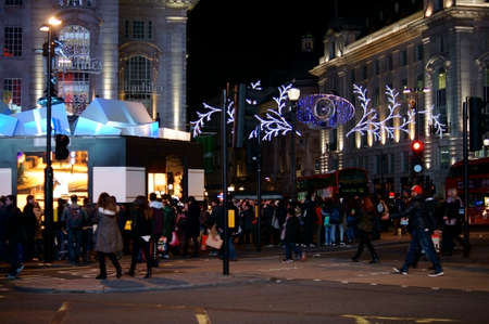 festively: London, UK November 29, 2014: A crowd of tourists and pedestrians are crossing a festively decorated intersection of the Piccadilly Circus on November 29, 2014 in London.