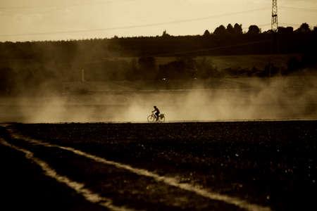loosen: A cyclist rides through the sputtered vapor of a tractor.