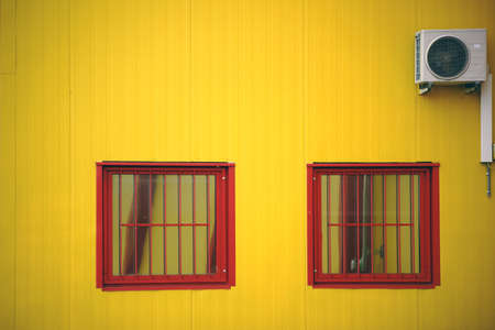 irregular shapes: The yellow side wall of a shopping mall with two barred windows and a fan.