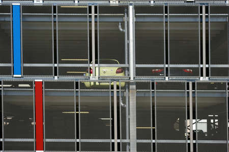 parking garage: An open parking garage with several parking decks protected by mesh wire.