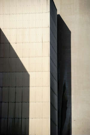 bedrijfshal: The corners and edges of an industrial building cast geometric shadows.