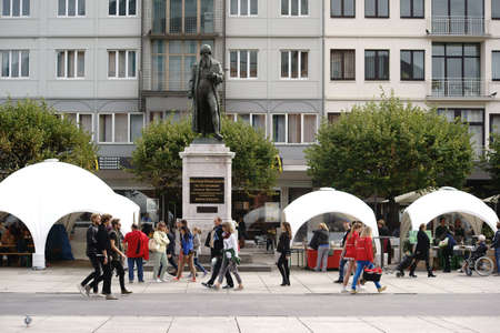 gutenberg: Mainz, Germany - September 25, 2015: Pedestrians crossing tents from a culinary market at the Gutenberg monument on the Gutenberg Square on September 25, 2015 in Mainz.
