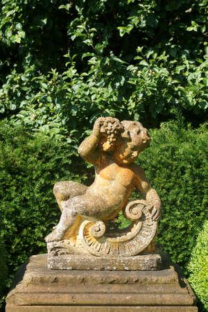 bacchus: The sculpture of a little boy, Bacchus, made of concrete for garden decoration.