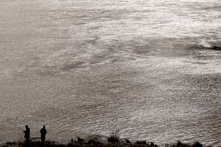 glimmer: The silhouettes of two anglers standing in the evening light on a glittering river.
