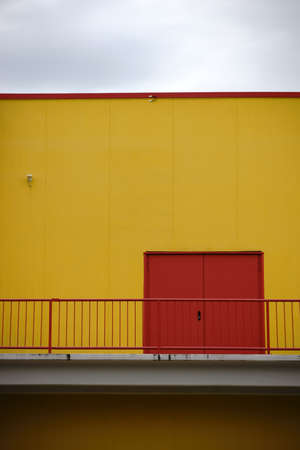 sidewall: A colorful and striking sidewall of a shopping center with an emergency exit and a railing on the first floor. Stock Photo