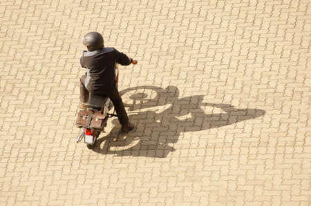 moped: The Aerial view of a moped, motorbike and driver, which casts a shadow.