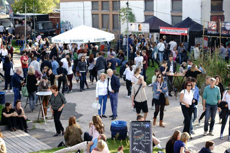 local festivals: Mainz, Germany October 02, 2015: Teenage viewers and visitors sit on wooden pallets and at beer tables or just going at the Streefood Festival on October 02, 2015 in Mainz.