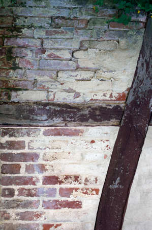 rotting: A rotting and mossy half-timbered house with bricks and beams.