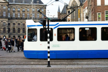dam square: Amsterdam, Netherlands - December 29, 2014: Group of people and a tram cross the Dam Square on December 29, 2014 in Amsterdam. Editorial