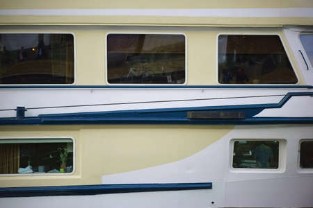 passenger ship: The side view of a passenger ship, starboard, with windows and railing. Stock Photo