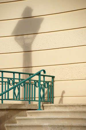 renovated: A newly renovated building wall with a lantern shadow and parts of a Stairs and Railings.